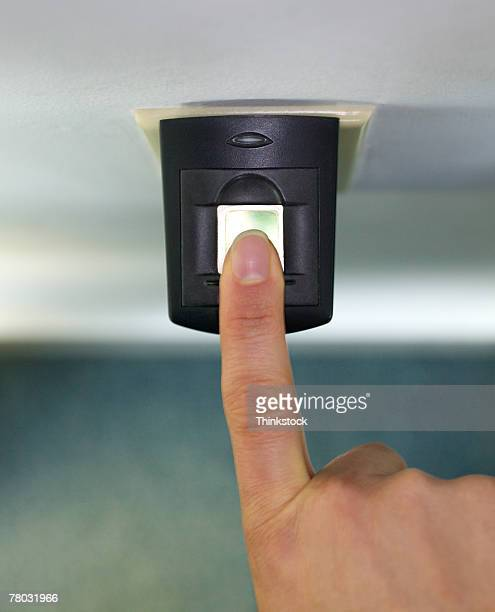 Close-up of a woman's finger on a fingerprint scanner security device