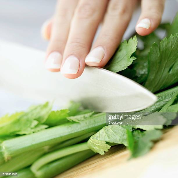 Close-up of a woman's hand chopping celery with a knife