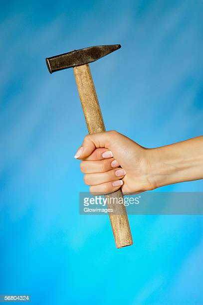 Close-up of a woman's hand holding a hammer