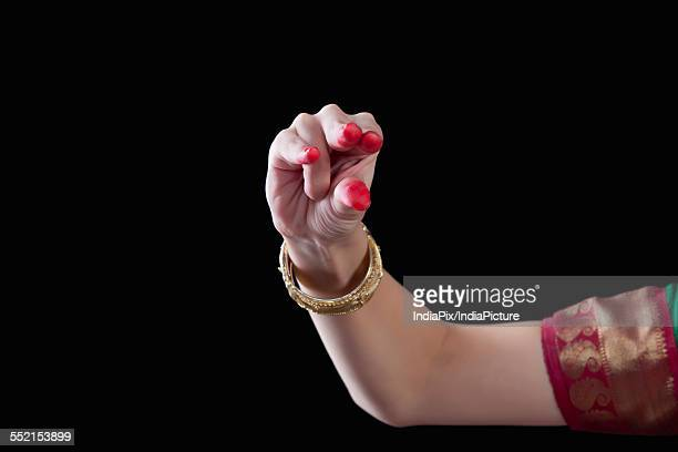 Close-up of a womans hand making Bharatanatyam gesture called Kangula on black background