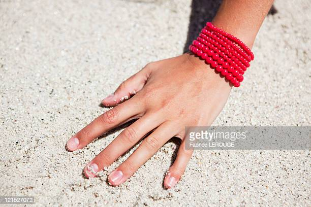 Close-up of a woman's hand on sand