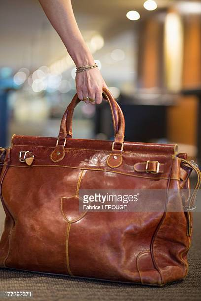close-up of a woman's hand picking up a leather purse - leather purse stock pictures, royalty-free photos & images