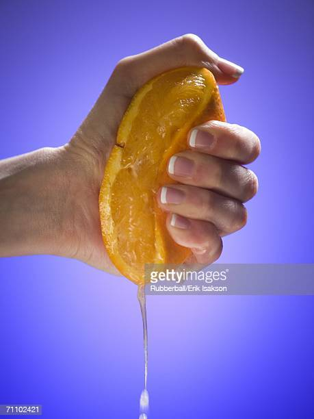 Close-up of a woman's hand squeezing an orange