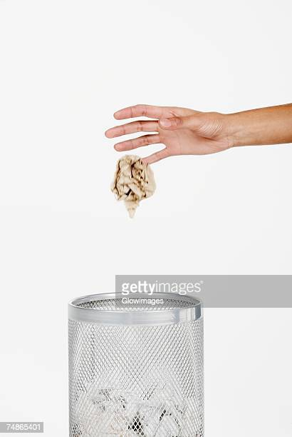 Close-up of a woman's hand throwing crumpled paper in a wastepaper basket