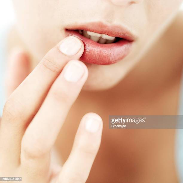 close-up of a woman's hand touching her lip - lip balm stock pictures, royalty-free photos & images