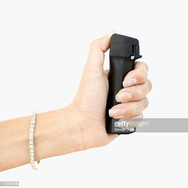 close-up of a woman's hand wearing a solitaire diamond bracelet holding a pepper spray - pepper spray stock pictures, royalty-free photos & images
