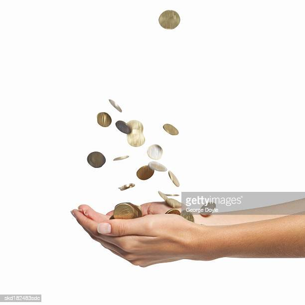 close-up of a woman's hands catching coins