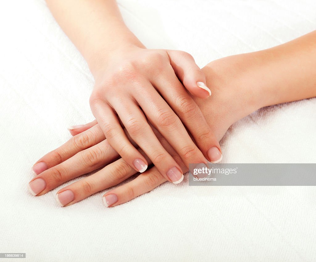 Close-up of a woman's hands crossed on a white background : Stock Photo