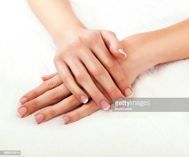 Close-up of a woman's hands crossed on a white background