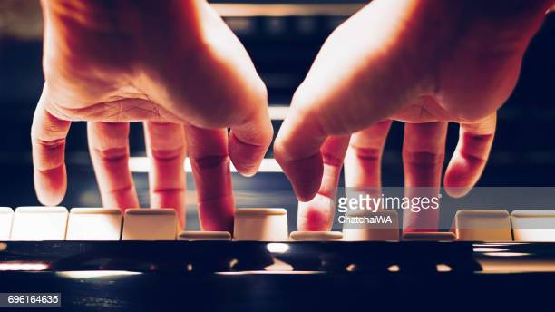 Close-up of a woman's hands playing the piano
