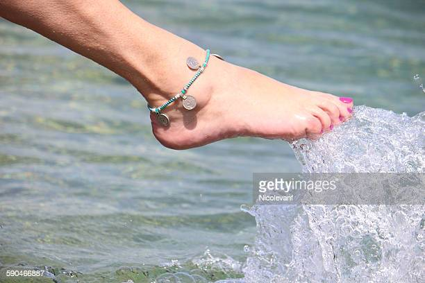 Close-up of a woman's leg splashing water in the sea