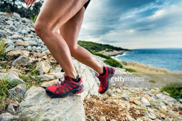Close-up of a woman's legs running up a rocky hill