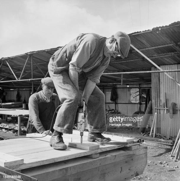 Close-up of a worker drilling screws into a wooden plank in a construction yard at the Solway Chemical Works in Whitehaven. Solway Chemicals Ltd were...