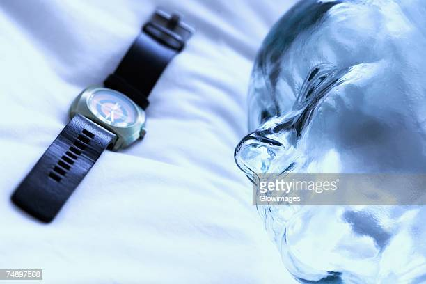 Close-up of a wristwatch with a glass statue