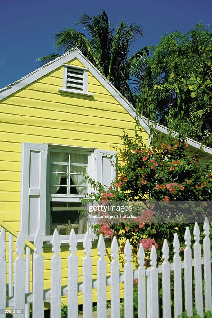 Close-up of a Yellow house with white shutters and white picket fence, Dunmore Town, Harbor Island, Bahamas : Stock Photo