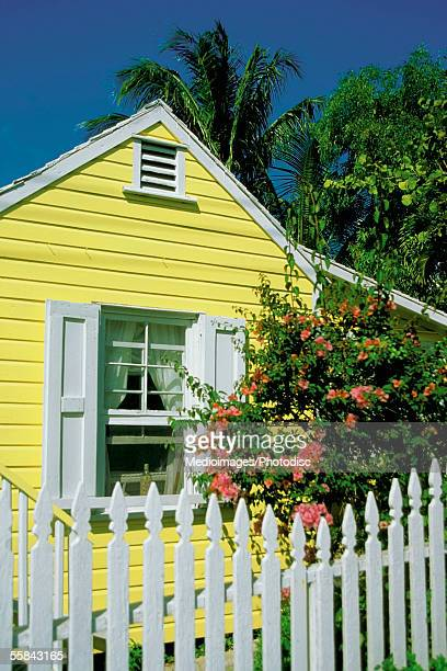 close-up of a yellow house with white shutters and white picket fence, dunmore town, harbor island, bahamas - ダンモアタウン ストックフォトと画像