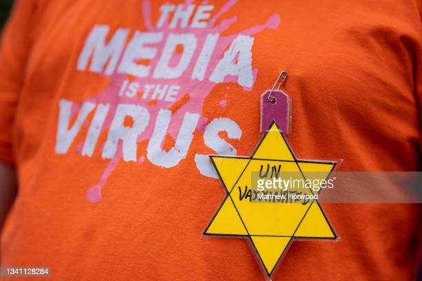 """Close-up of a yellow star containing the words """"unvaccinated"""" on the shirt of a protestor during a protest against vaccine passports on September 18,..."""