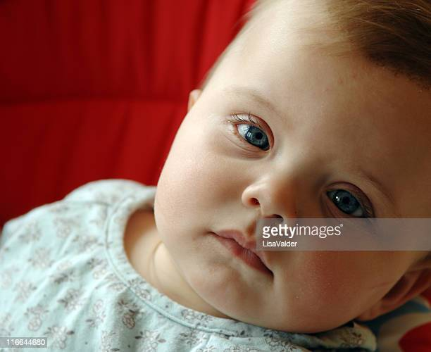 close-up of a young baby on red cushions - conjunctivitis stock pictures, royalty-free photos & images