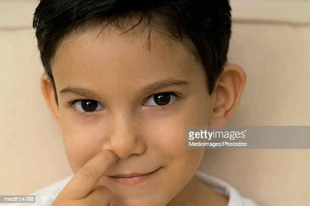 Close-up of a young boy picking his nose