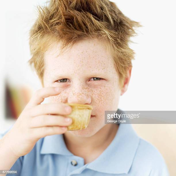 Close-up of a young boy (8-10) smelling a muffin