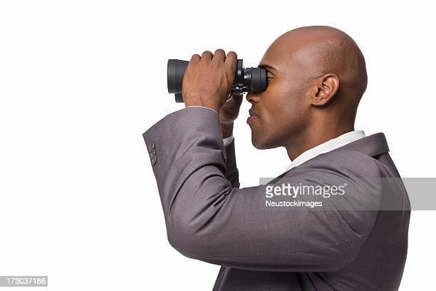 Closeup of a young businessman looking through binoculars