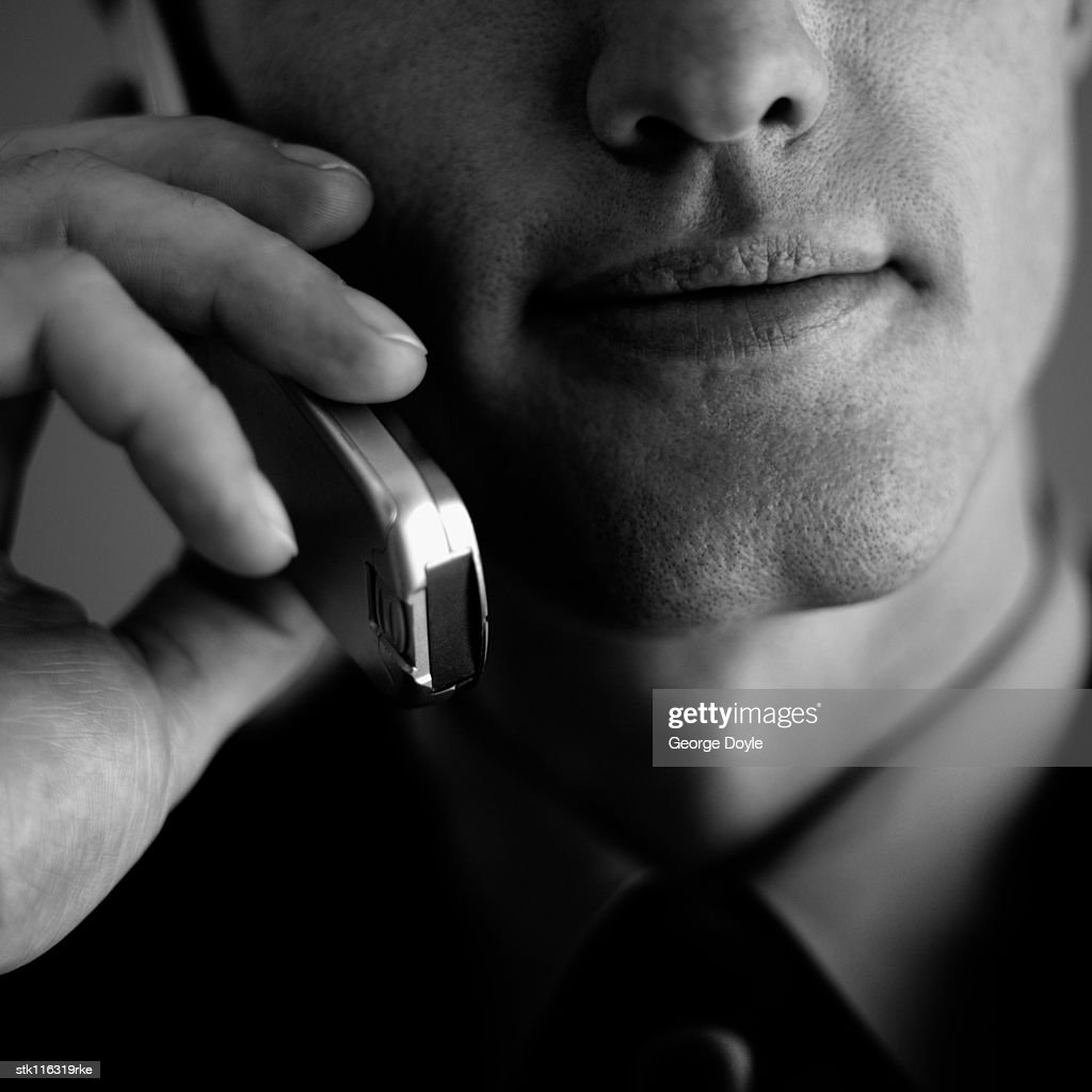 Close-up of a young businessman talking on a mobile phone : Stock Photo