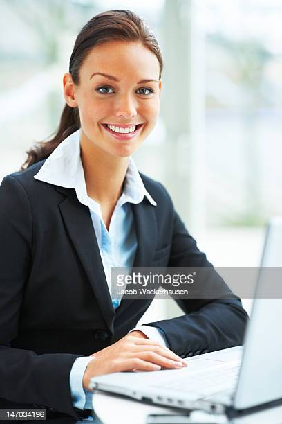 close-up of a young businesswoman using laptop and smiling - businesswear stock pictures, royalty-free photos & images