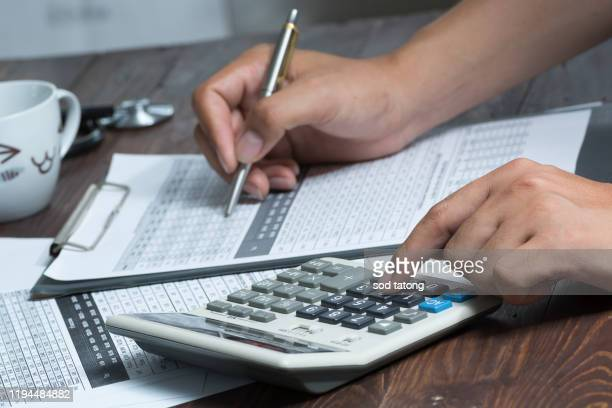 closeup of a young caucasian healthcare professional wearing a white coat calculates on an electronic calculator - erschwinglich stock-fotos und bilder
