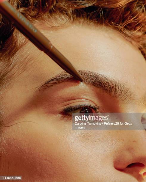 closeup of a young confident woman filling in her eyebrows - 眼眉 個照片及圖片檔
