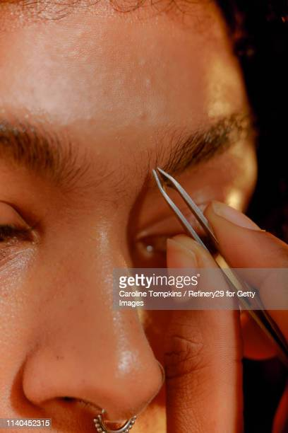 closeup of a young confident woman plucking her eyebrows - 修眉 個照片及圖片檔