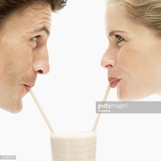 Close-up of a young couple drinking a milkshake from a glass with straws