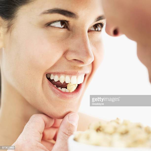 Close-up of a young couple eating cashew nuts from a bowl