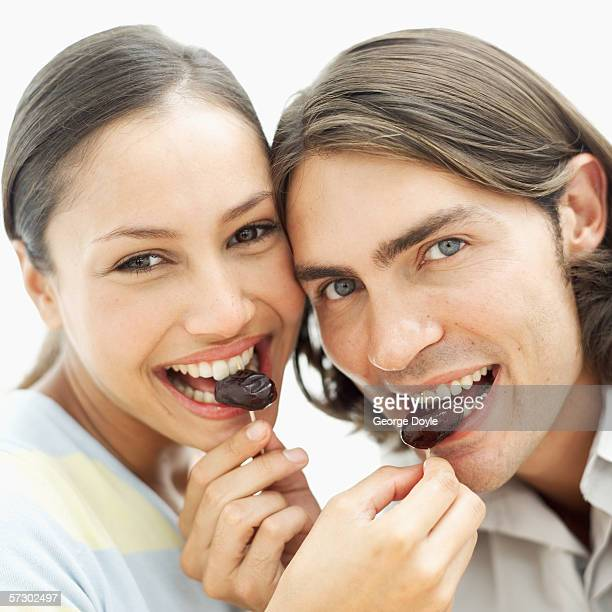 close-up of a young couple feeding each other prunes - dörrpflaume stock-fotos und bilder