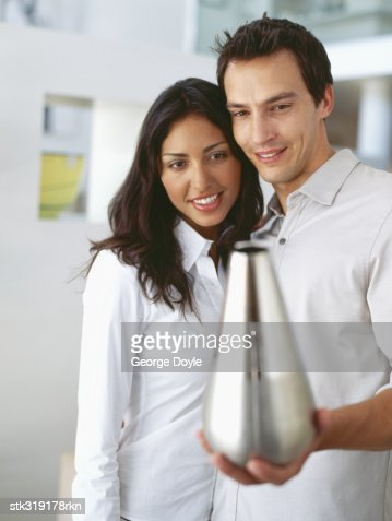 Closeup Of A Young Couple Holding An Empty Vase Stock Photo Getty
