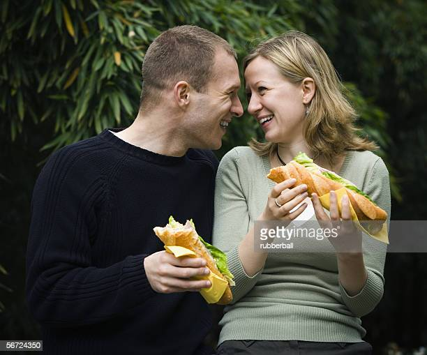 close-up of a young couple holding sandwiches - submarine sandwich stock pictures, royalty-free photos & images