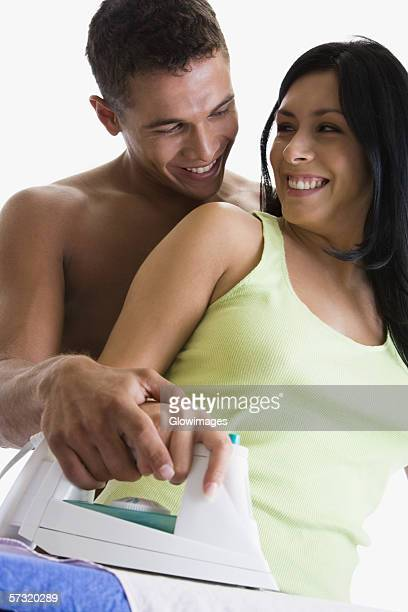 Close-up of a young couple ironing on an ironing board
