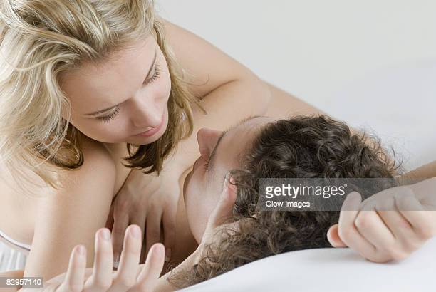 Close-up of a young couple lying on the bed and romancing