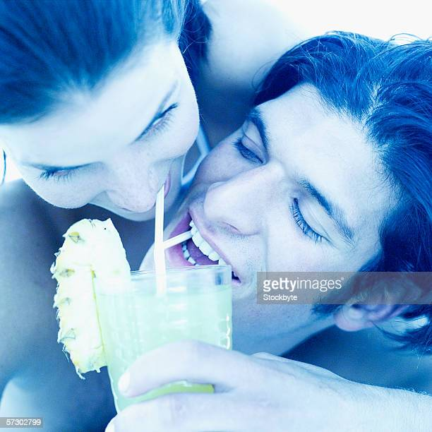 Close-up of a young couple sharing a glass of pineapple juice