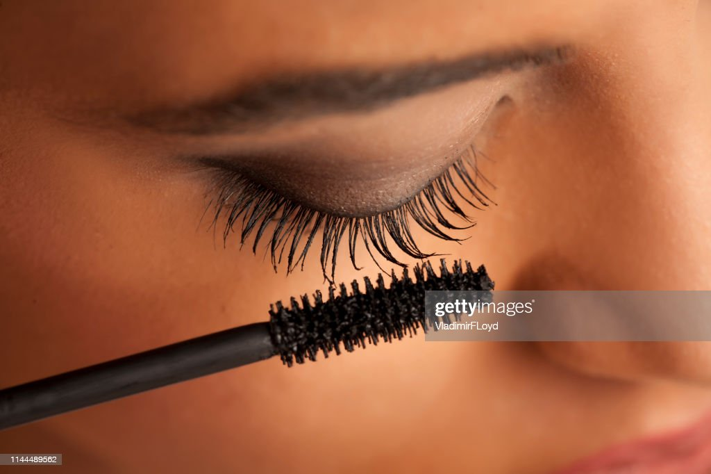 closeup of a young dark-skinned woman applying mascara on a white background : Stock Photo