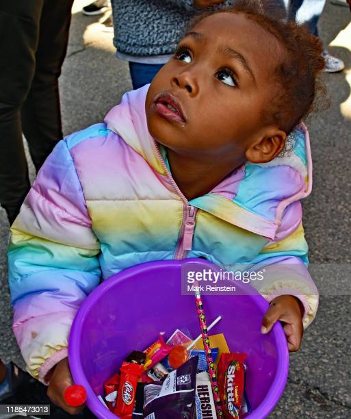 Closeup of a young girl as she holds a bucket of candy during the Day of the Dead parade Emporia Kansas October 26 2019