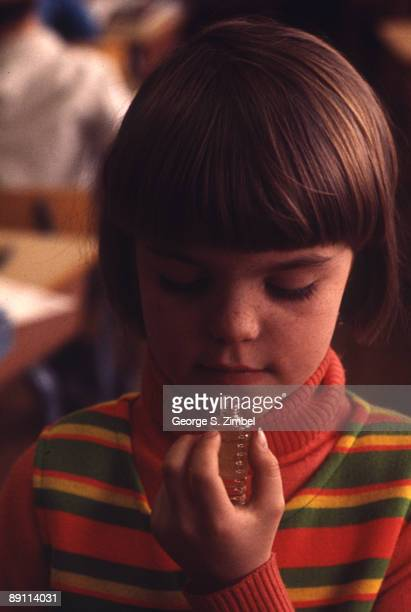 Close-up of a young girl as she smells the aroma from a small bottle, Peekskill, New York, late 1960s.