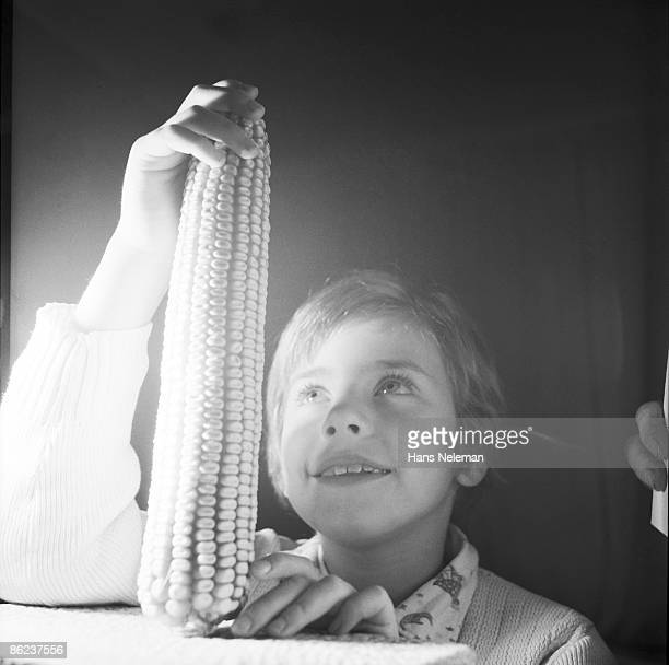 Close-up of a young girl as she smiles at an illuminated ear of corn, Santiago, Santiago Region, Chile, November 1960.