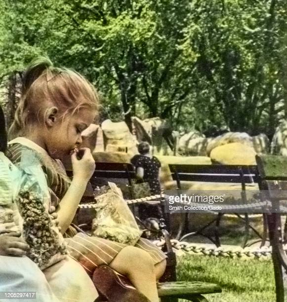 Close-up of a young girl sitting on a park bench in an outdoor setting and contemplatively eating kettle corn from a bag, Detroit, Michigan, 1960....