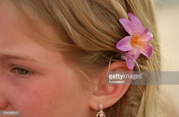 Close-up of a young girl (14-15) wearing a flower behind her ear