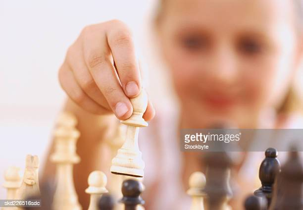 Close-up of a young girl's hand lifting a chess piece