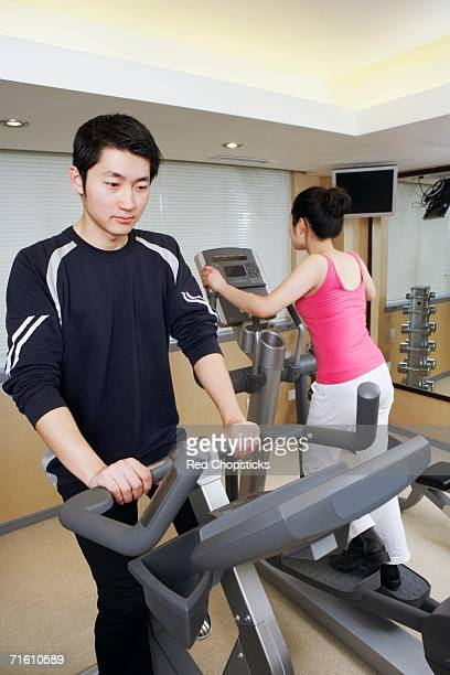 Close-up of a young man and a young woman exercising in a gym