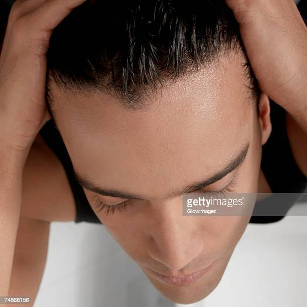 Close-up of a young man applying hair gel