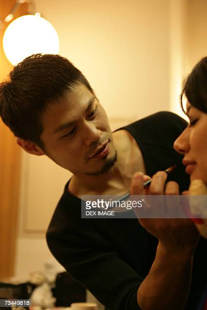 Close-up of a young man applying lip liner on a young woman's lips