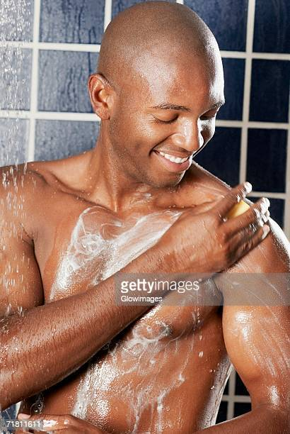 Close-up of a young man applying soap on his body