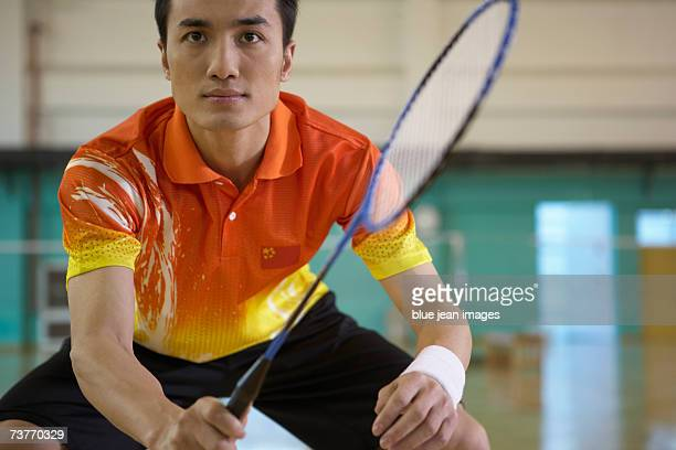 Close-up of a young man as he crouches and holds his racket, ready for a game of badminton.